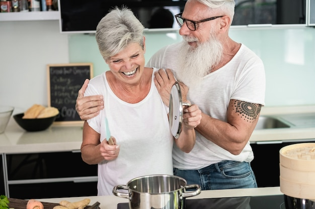 Happy senior couple enjoying and cooking healthy dinner together at home - focus on faces