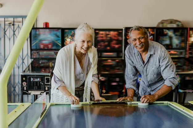 Happy senior couple enjoying a game of table hockey inside of a game arcade