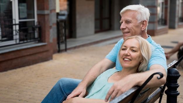 屋外のベンチで自分の時間を楽しんで幸せな先輩カップル