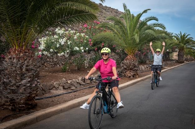 행복한 노년 부부는 전기 자전거, 재미있는 은퇴 개념으로 스포츠 활동을 즐깁니다. 백그라운드에서 야자수와 꽃