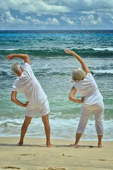 Счастливая пара старших, тренирующихся летом на берегу моря