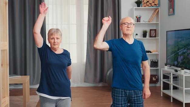 요가 매트에서 함께 운동하는 행복한 노부부. 노인 건강하고 활동적인 생활 방식 운동 및 집에서 운동, 노인 훈련 및 피트니스