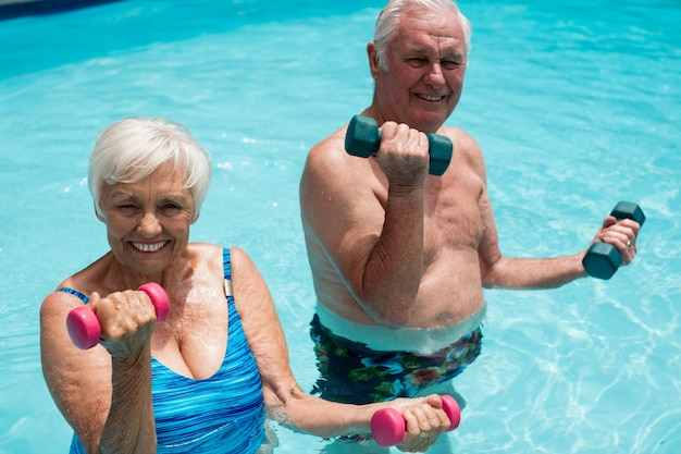 수영장에서 아령으로 운동하는 행복 한 노인 부부