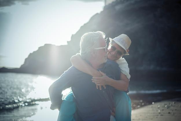 Счастливая старшая пара развлекается и наслаждается активным отдыхом на пляже