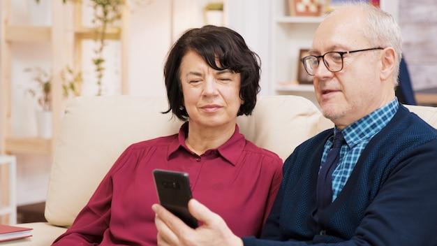 リビングルームのソファに座ってビデオ通話をしている幸せな年配のカップル。現代の技術を使用して老夫婦