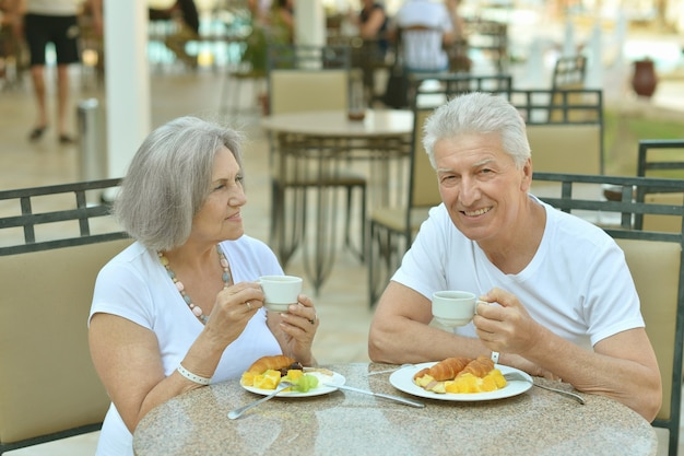 Happy senior couple having breakfast in cafe