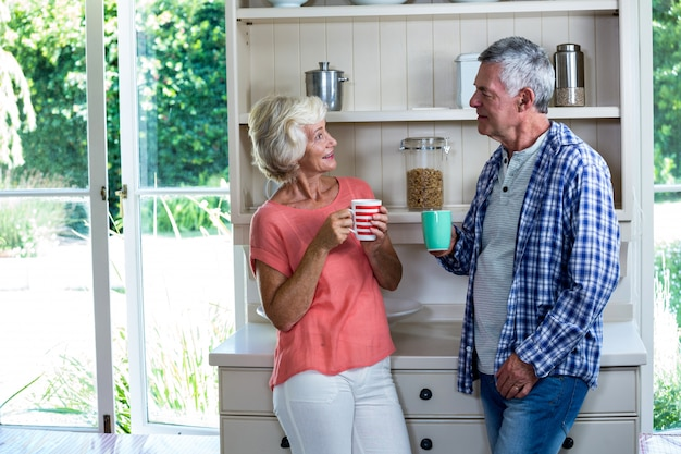Happy senior couple having coffee at home