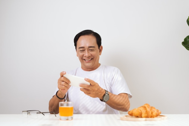 Happy senior couple having croissant breakfast at home and drinking orange juice, using smartphone.