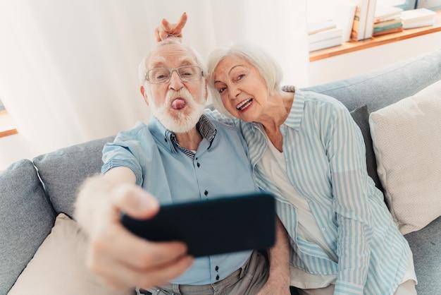 즐거운 시간을 보내고 온라인으로 공유하기 위해 휴대전화로 사진을 찍는 행복한 노부부