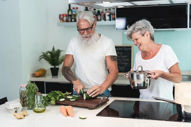 家で一緒に料理を楽しんでいる幸せな年配のカップル-キュウリを刻む男の手に主な焦点