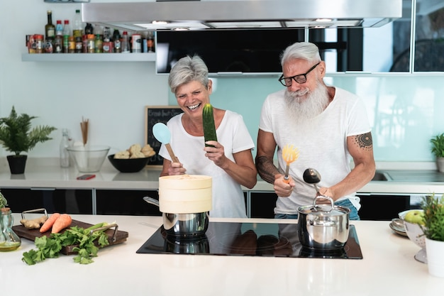 Happy senior couple having fun dancing and cooking together at home - main focus on senior man face