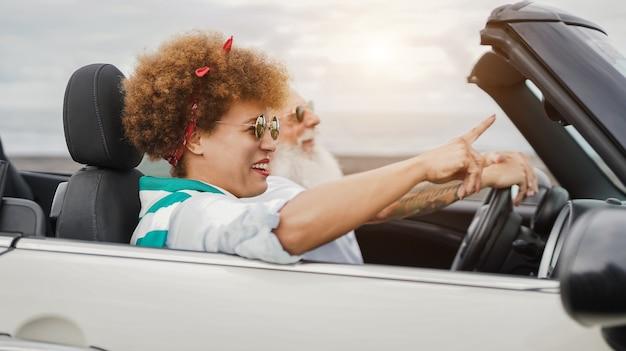 여름 방학 동안 컨버터블 자동차에서 즐거운 시간을 보내는 행복한 노부부 - 아프리카 여성의 얼굴에 초점