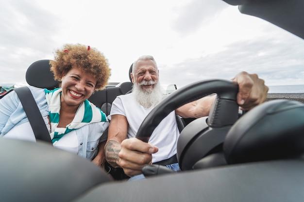 夏休み中にコンバーチブル車で楽しんでいる幸せな年配のカップル-流行に敏感な男の顔に焦点を当てる