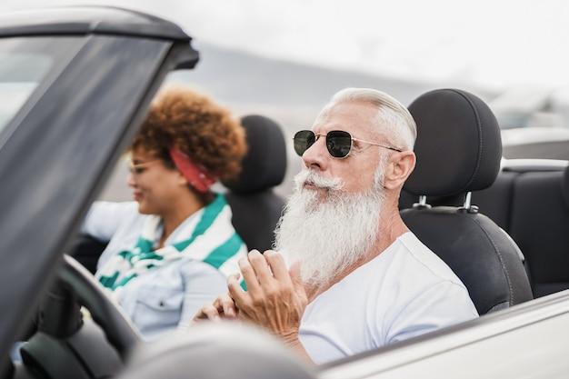 여름 방학 동안 컨버터블 자동차에서 즐거운 시간을 보내는 행복한 노부부 - 노인의 얼굴에 초점