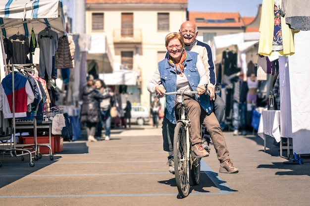 Happy senior couple having fun with bicycle at flea market