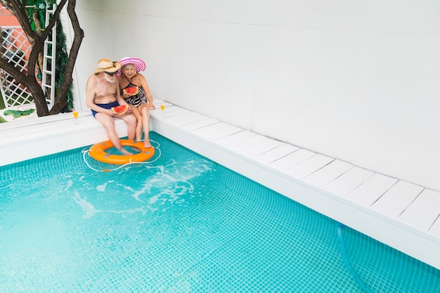 Happy senior couple having party in the swimming pool