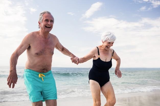手をつないでビーチで走っている幸せな年配のカップル