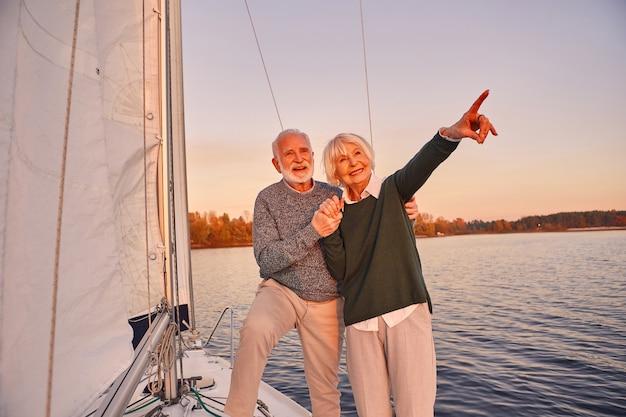 浮かんでいるヨットの甲板の横に立って手をつないで笑っている幸せな年配のカップル