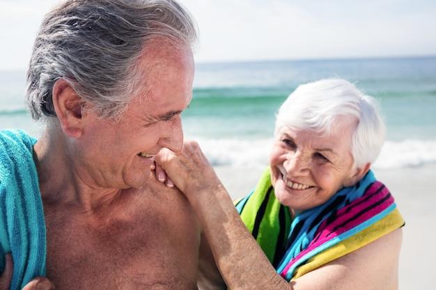 Happy senior couple holding a towel around neck
