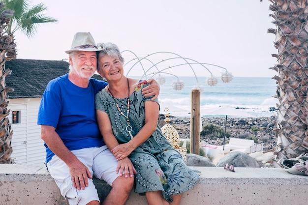 幸せな年配のカップルは愛を込めて抱きしめ、一緒に屋外のレジャー活動をお楽しみください
