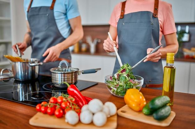 Счастливая старшая пара в фартуках готовит пасту и свежий салат на кухне и хорошо проводит время.