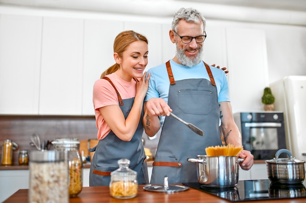 Счастливая старшая пара в фартуках готовит макароны на кухне и хорошо проводит время.