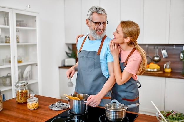 エプロンで幸せな年配のカップルがキッチンでパスタを準備し、楽しい時間を過ごしています。
