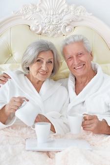 Счастливая пара старших в постели с кофе
