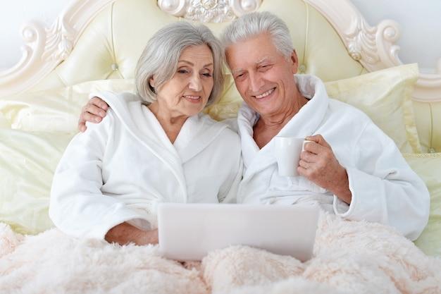 Счастливая старшая пара в постели с ноутбуком
