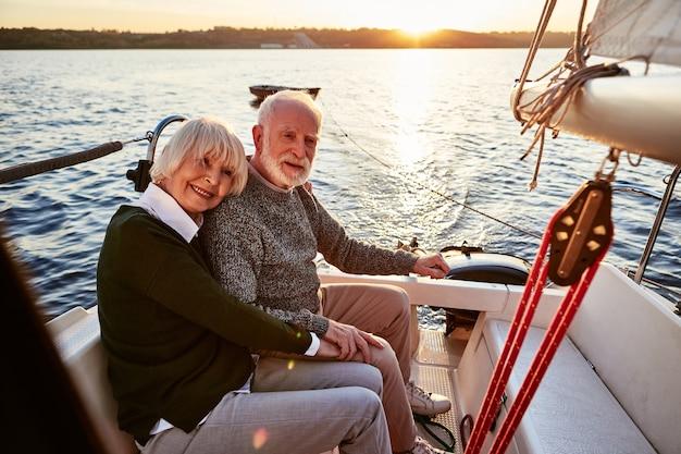 抱き合って一緒に時間を過ごす手をつないでいる老人と女性を愛する幸せな年配のカップル