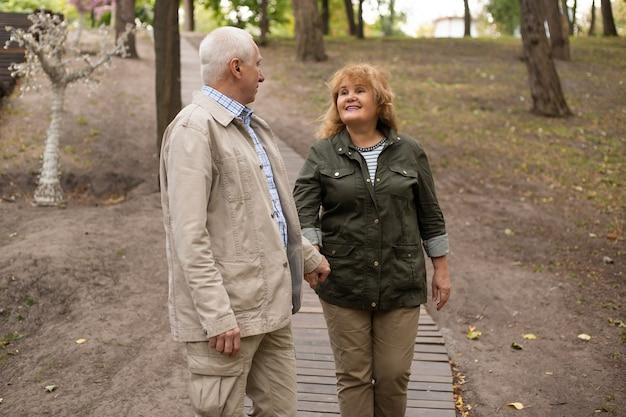 秋の自然の中を散歩するのが大好きな幸せな年配のカップル、春の時間にリラックスした年配のカップル。