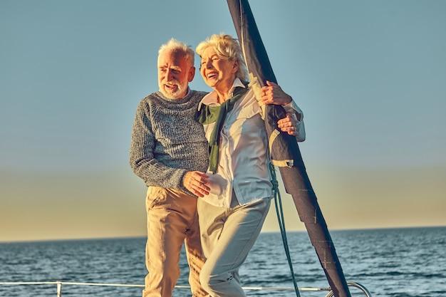 ヨットやヨットのデッキの横に立っている愛の引退した男性と女性の幸せな年配のカップル