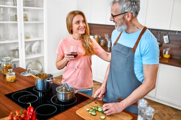 Счастливая пара старших на кухне. зрелый мужчина в фартуке готовит романтический ужин для своей жены.