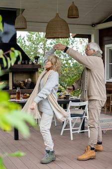 Счастливая старшая пара в теплой стильной повседневной одежде танцует на деревянном полу патио у своего загородного дома против сервированного стола и камина