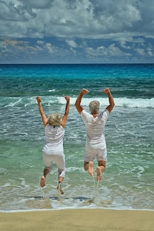 Happy senior couple jumping in summer on  seashore