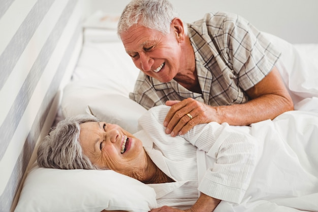 Happy senior couple laughing on bed in bedroom