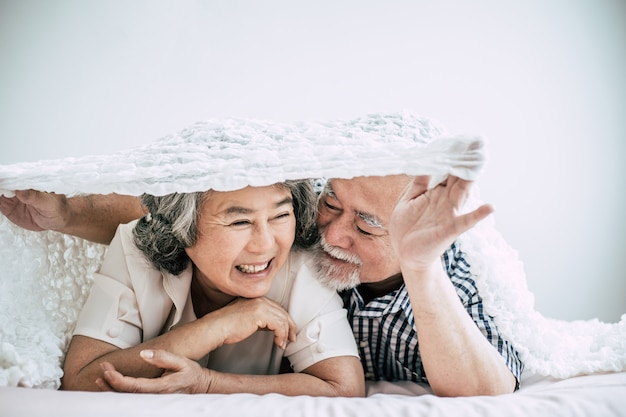 Happy senior couple laughing in bedroom