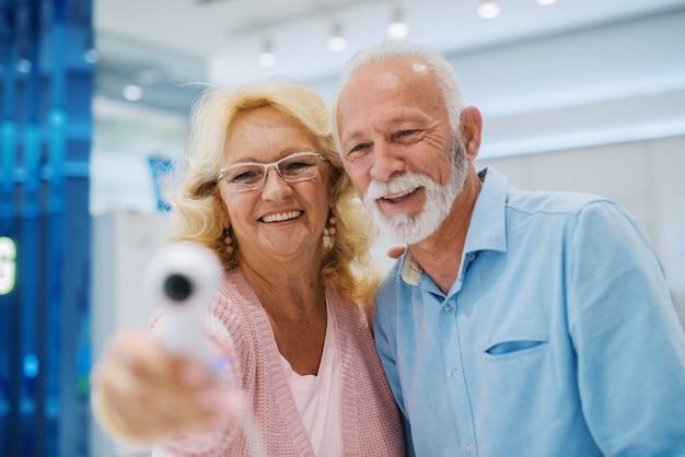 幸せな先輩カップルがお互いを見て、360度カメラを試してみます。テックストアのインテリア。カップルにセレクティブフォーカス。