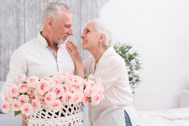 Happy senior couple looking at each other holding basket of roses in hand
