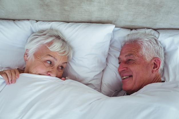 Happy senior couple looking at each other while lying on bed