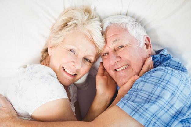 Happy senior couple lying on bed
