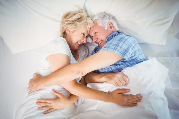 Happy senior couple lying on bed