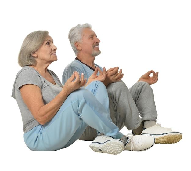 Счастливая пара старших медитирует на белом фоне