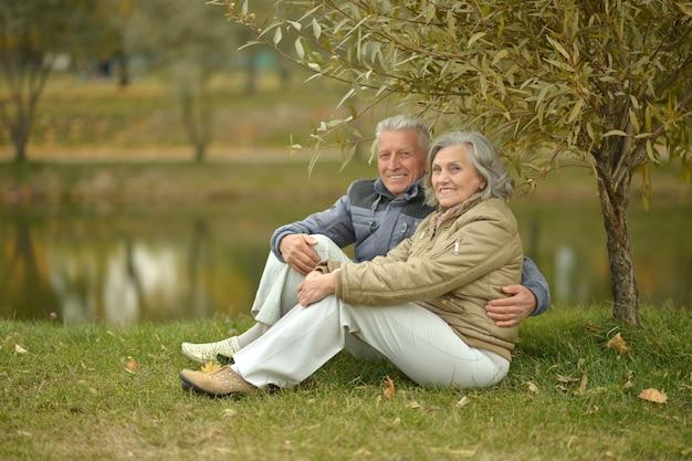 秋の川の近くの幸せな年配のカップル、ぼやけた背景