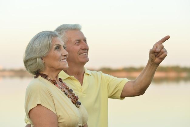 여름에 강 근처의 행복한 노부부, 손으로 가리키는 남자