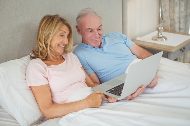 ラップトップを使用してベッドで幸せな先輩カップル