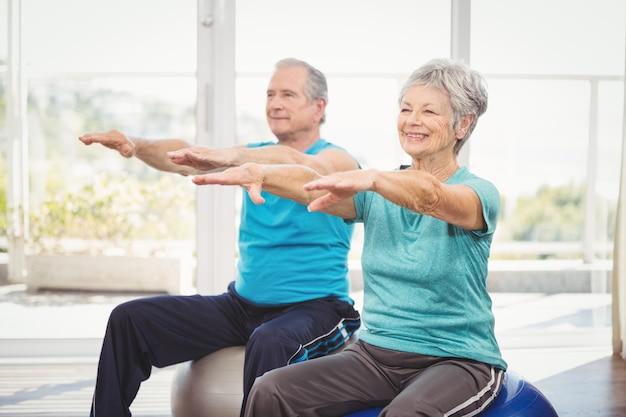 Счастливая пара старших выполняет упражнения
