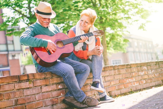 Happy senior couple playing a guitar while sitting outside on a wall on a sunny day