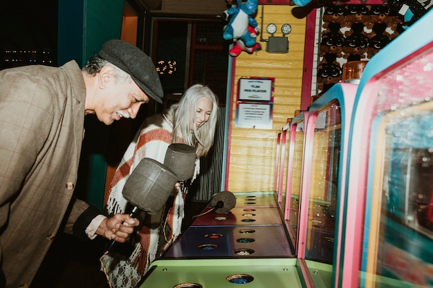 ゲームセンターでモグラたたきをしている幸せな年配のカップル