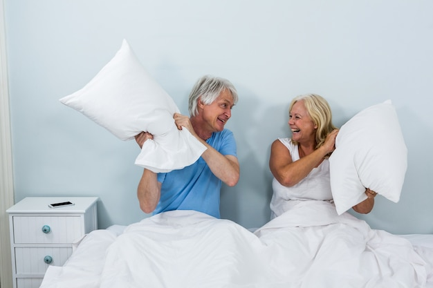 Happy senior couple playing with pillows in bedroom